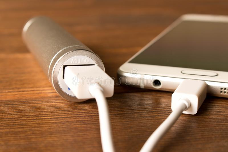 Smartphone de carregamento do banco de prata do poder na tabela de madeira fotos de stock royalty free