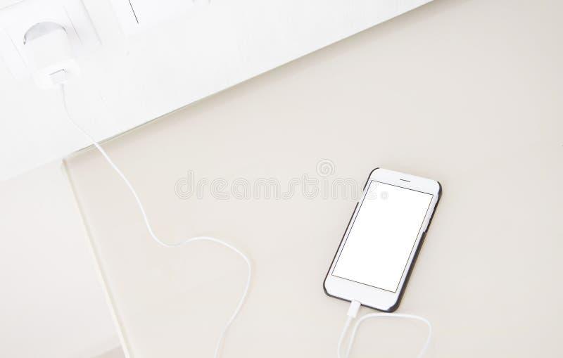 Smartphone de carregamento, telefone celular na tabela de madeira, telefone celular da tela vazia Foco seletivo Copie o espaço, a imagem de stock royalty free