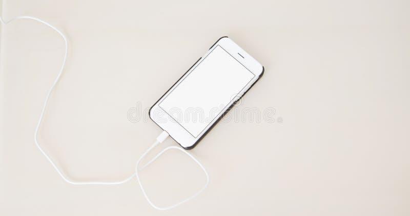 Smartphone de carregamento, telefone celular na tabela de madeira, telefone celular da tela vazia Foco seletivo Copie o espaço, a imagem de stock