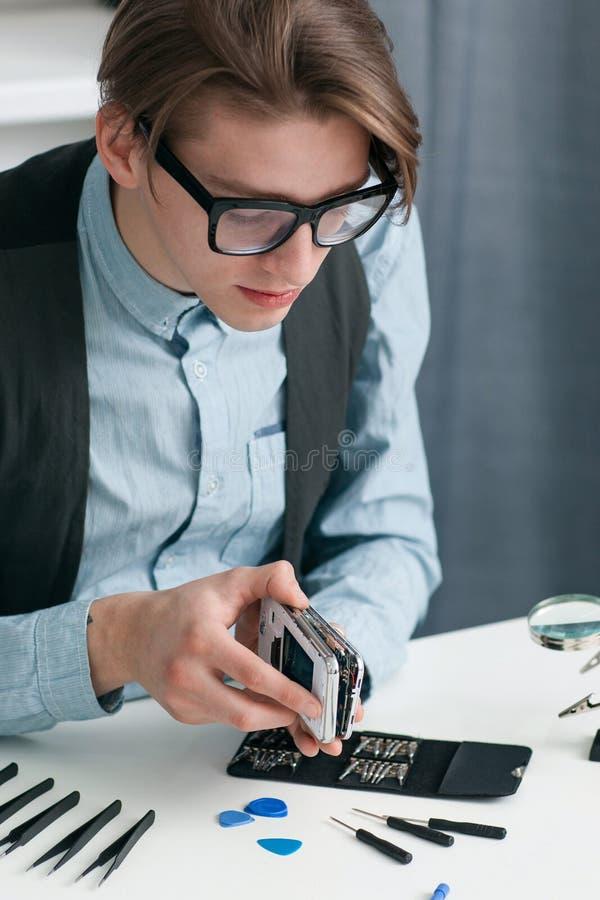 Smartphone de desmontada do homem na oficina de reparações imagem de stock
