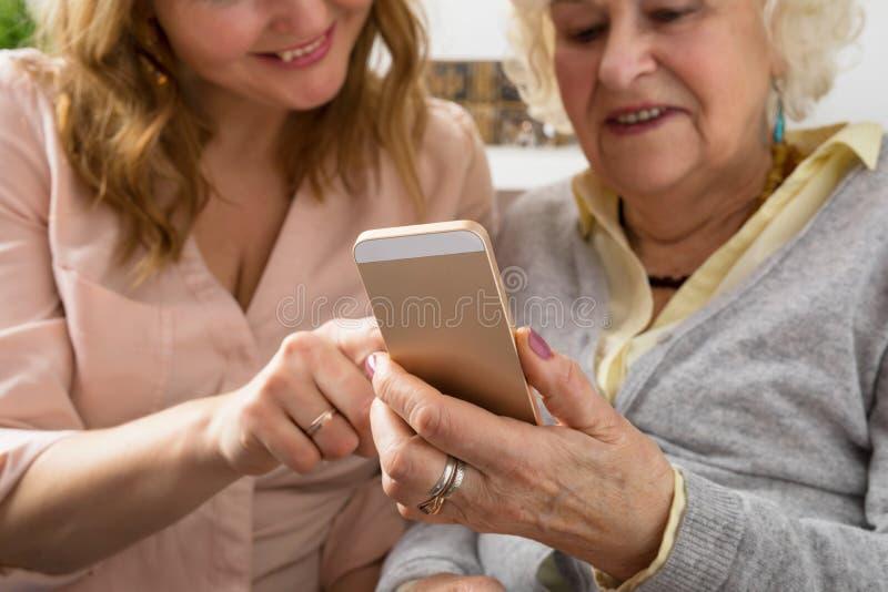Smartphone de exploración de la abuela y de la nieta fotografía de archivo