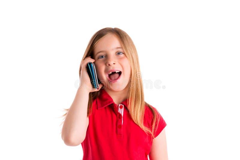 Smartphone de fala de sorriso recortado louro da menina fotografia de stock