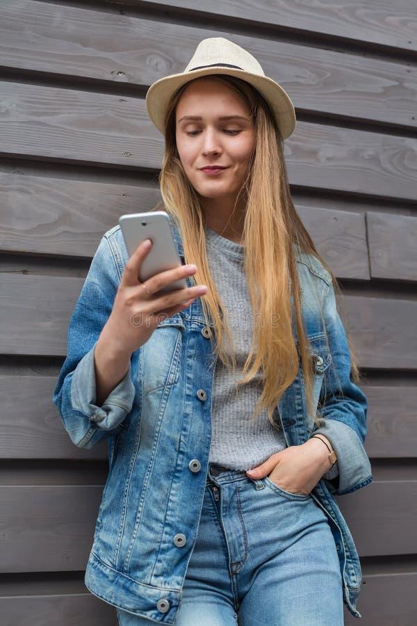 Smartphone de l'adolescence de femme en dehors du mur en bois photographie stock libre de droits