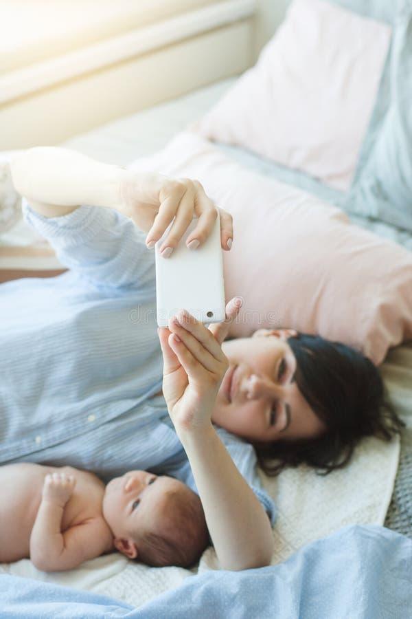 Smartphone de la charla de la comunicación de la familia recién nacido imágenes de archivo libres de regalías