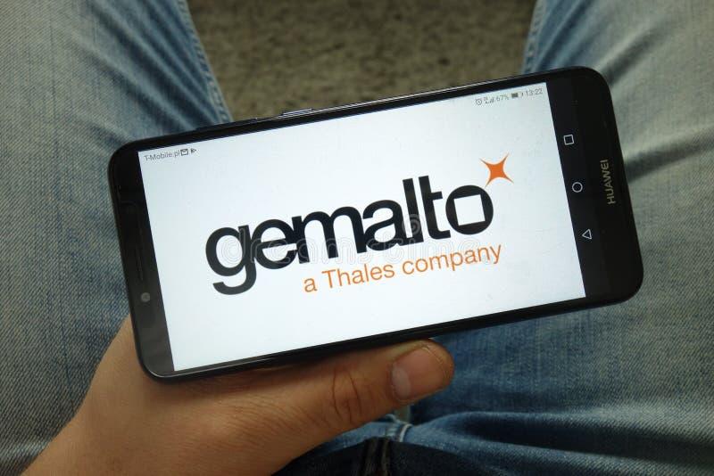 Smartphone de la tenencia del hombre con el logotipo digital de la compañía de seguridad de Gemalto imagenes de archivo