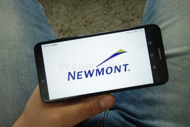 Smartphone de la tenencia del hombre con el logotipo de Newmont Mining Corporation imagen de archivo libre de regalías
