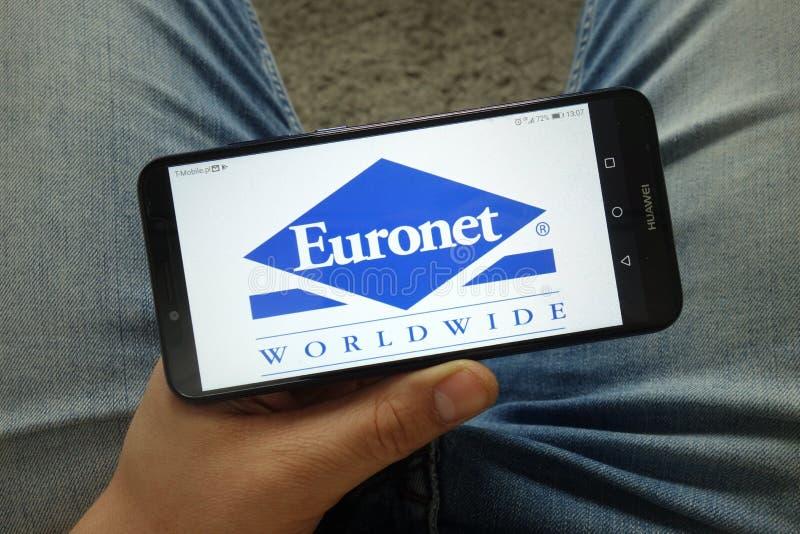 Smartphone de la tenencia del hombre con Euronet Worldwide, Inc Insignia de la compa??a imagenes de archivo