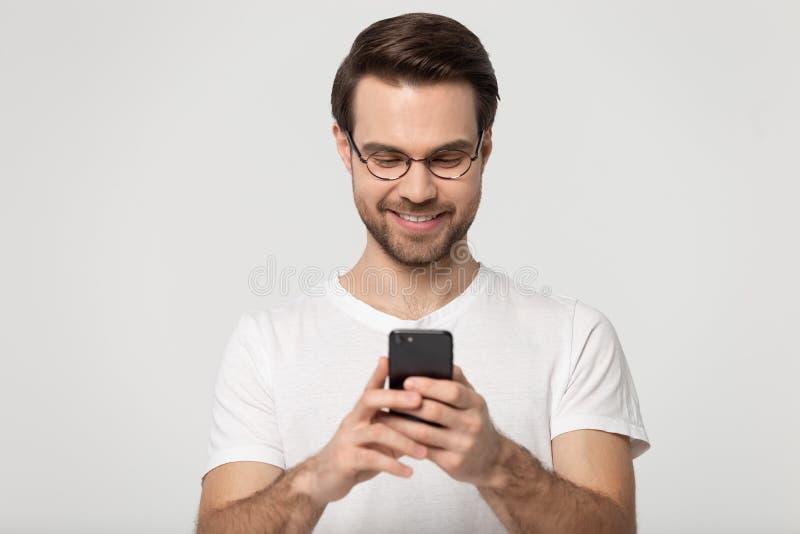 Smartphone de la tenencia del hombre que charla con el tiro en línea del estudio de los amigos fotografía de archivo