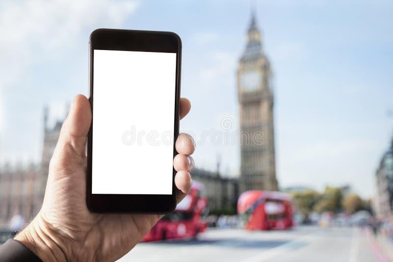 Smartphone de la tenencia de la mano con la pantalla en blanco en Londres imagen de archivo libre de regalías