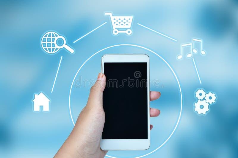Smartphone de la tenencia de la mano con tecnología del negocio y de Internet foto de archivo libre de regalías