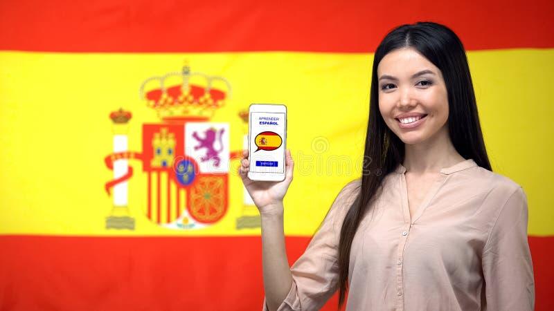 Smartphone de la tenencia de la muchacha con el app del estudio de la lengua, bandera española en fondo foto de archivo