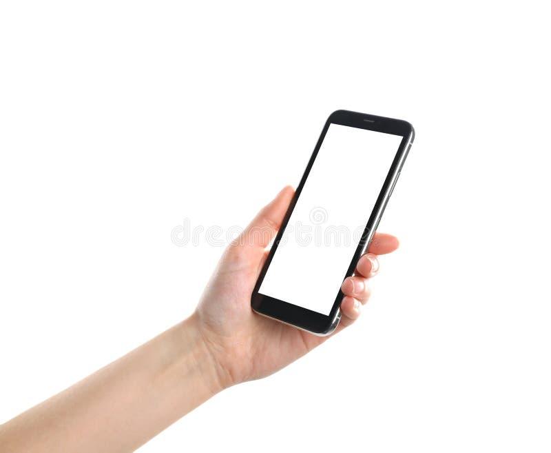 Smartphone de la tenencia de la mujer con la pantalla en blanco en el fondo blanco, primer de la mano imagen de archivo libre de regalías