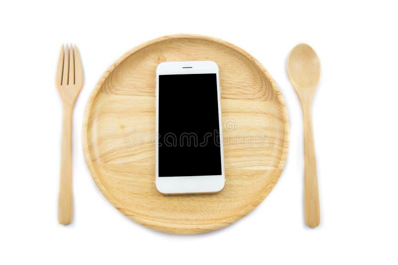 Smartphone de la visión superior en plato de madera con el spon y bifurcación en el fondo blanco fotos de archivo