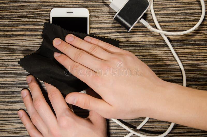 Smartphone de nettoyage avec un tissu de microfiber image stock