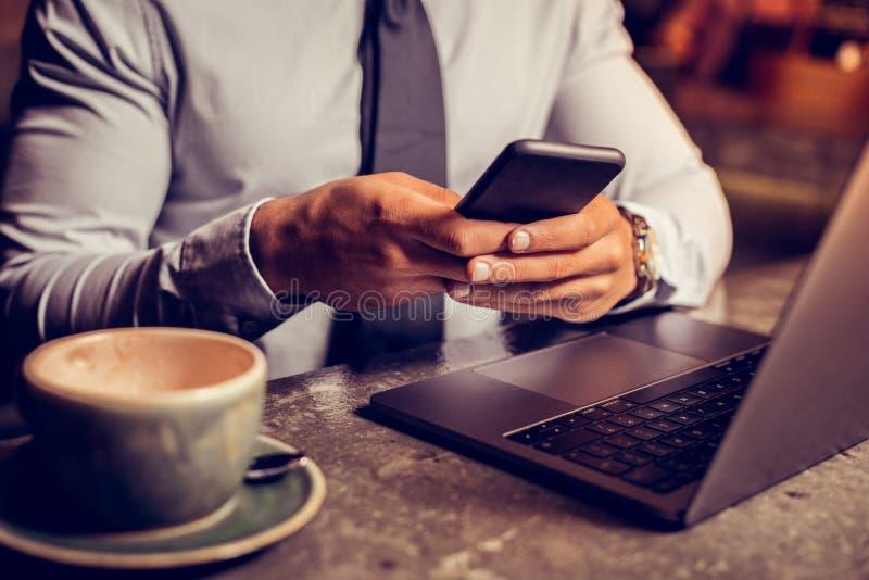 Smartphone de participation d'homme d'affaires dans des ses mains après avoir bu du café images libres de droits