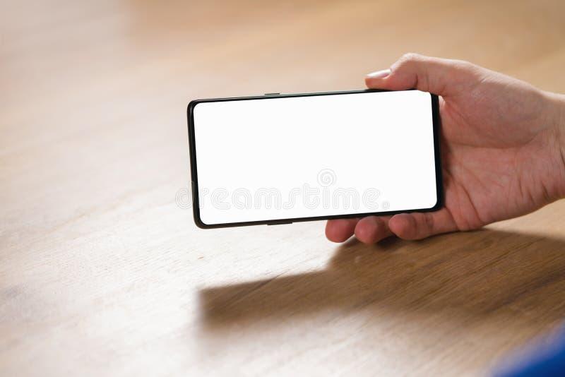 Smartphone de participation de main de jeune homme avec l'écran blanc vide en en largeur image stock