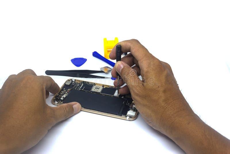 Smartphone de réparation d'homme de main avec des outils, isolat, le besoin de dommages de smartphone de réparer images libres de droits