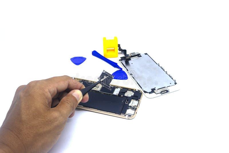 Smartphone de réparation d'homme de main avec des outils, isolat, le besoin de dommages de smartphone de réparer photographie stock