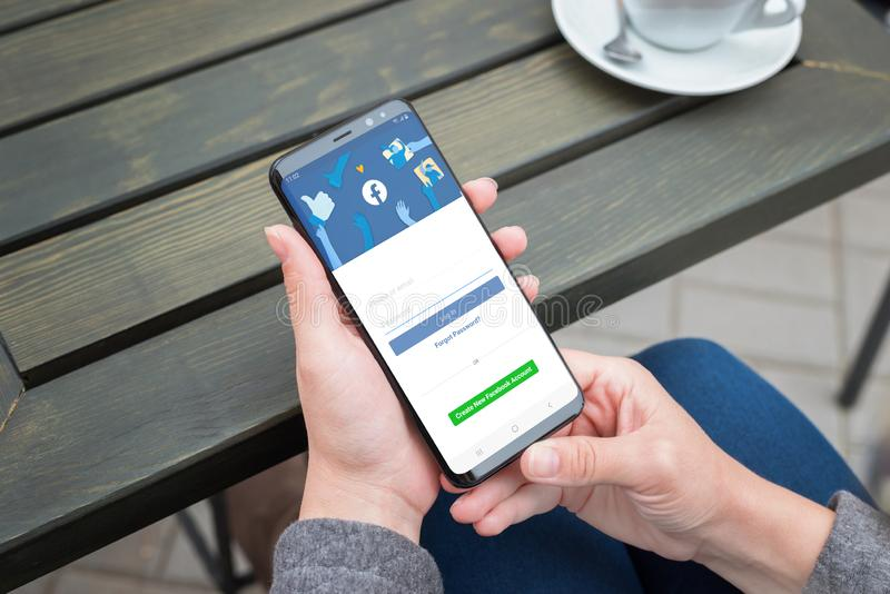 Smartphone de Samsung Galaxy d'utilisation de femme à ouvrir une session sur le compte social de réseau de Facebook image libre de droits
