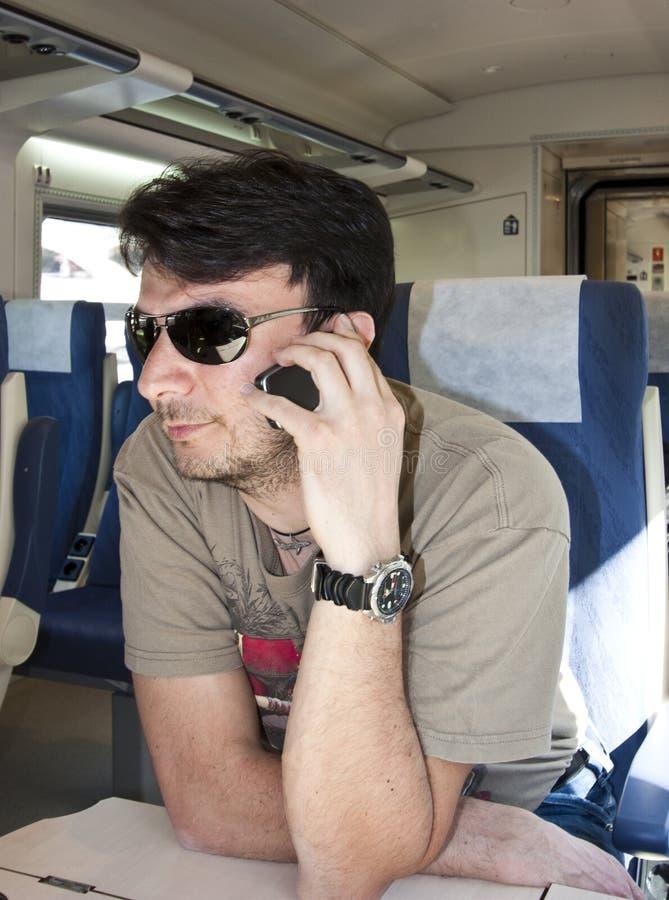 Smartphone de utilização adulto no trem imagem de stock