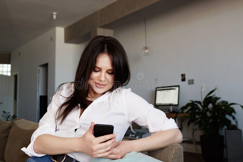 Smartphone de utilização fêmea da morena nova feliz que relaxa no sofá na sala de visitas fotos de stock
