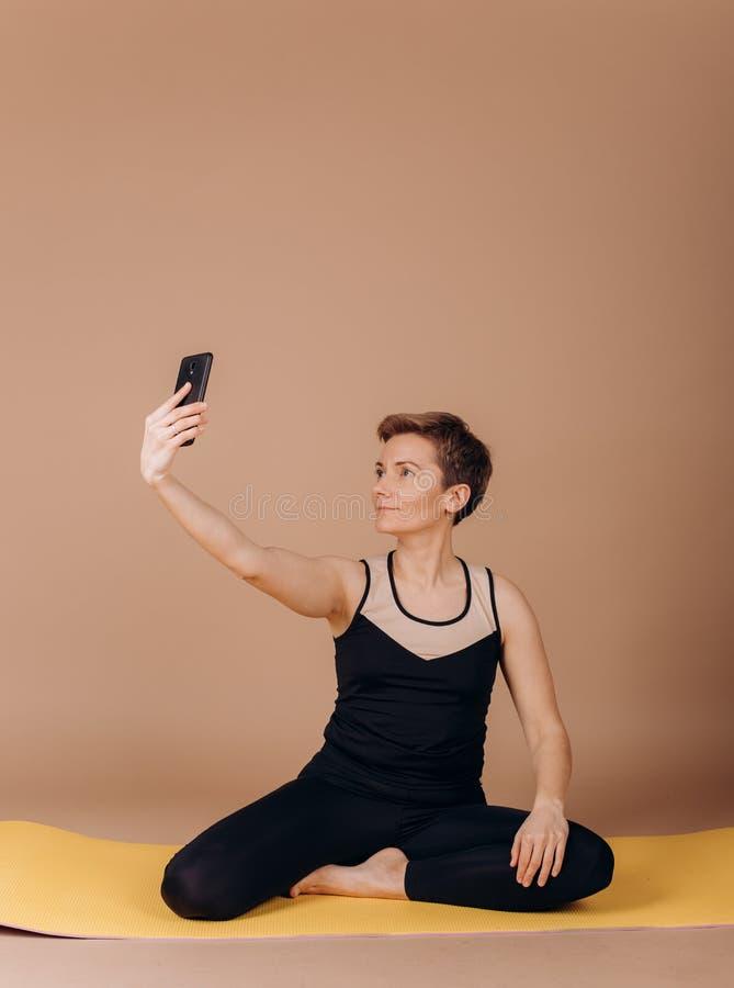 Smartphone del carimat de los pilates de la yoga de la aptitud del deporte de la muchacha foto de archivo