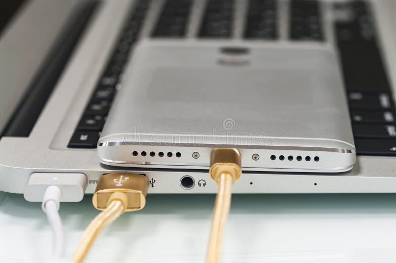Smartphone del collegamento con un cavo del usb al computer portatile fotografie stock