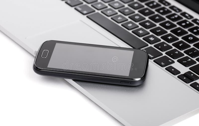 Smartphone del negocio en el ordenador portátil imagenes de archivo
