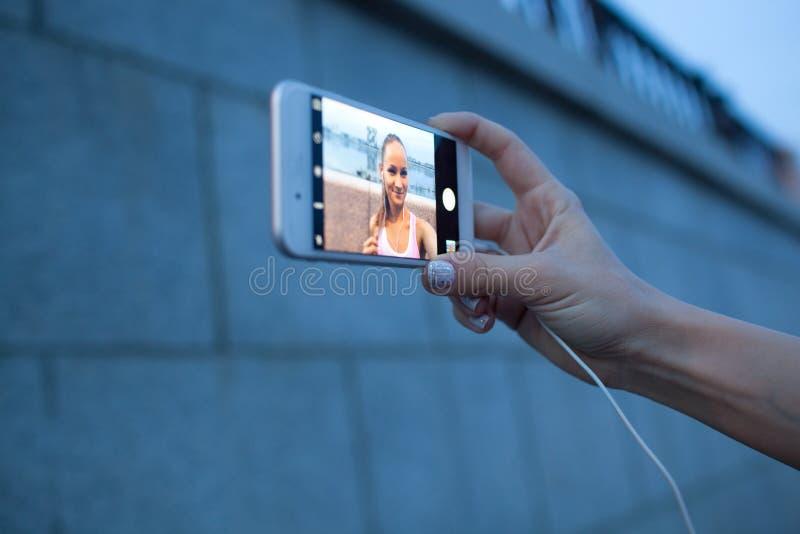 Smartphone del primer en la mano de la mujer que hace el selfie fotografía de archivo libre de regalías