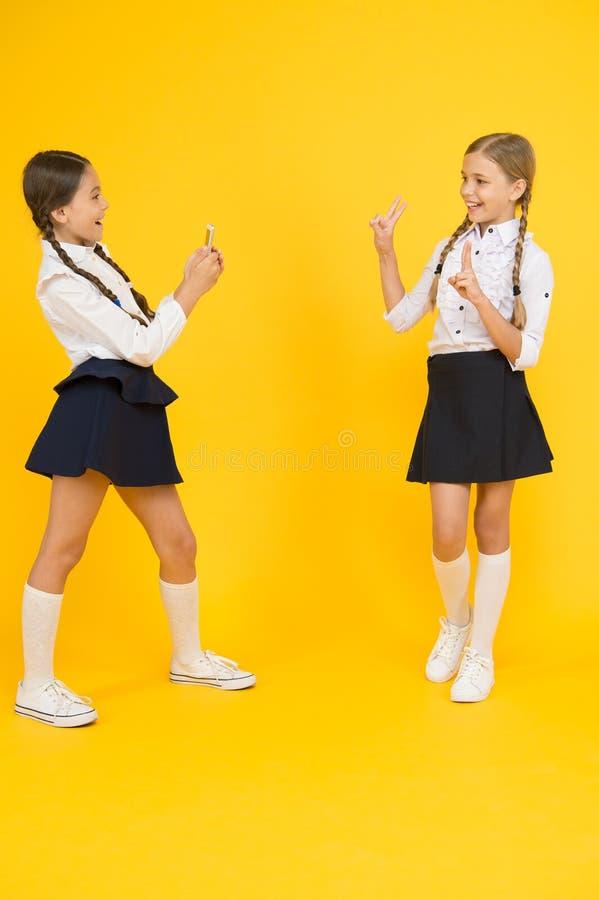 Smartphone del uso de la escuela Las colegialas utilizan smartphone para tomar la foto Uniforme escolar de las muchachas Blog per foto de archivo