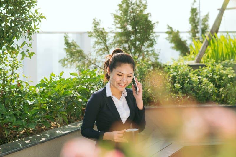 Smartphone del uso de la mujer de negocios en el parque del jardín imagen de archivo