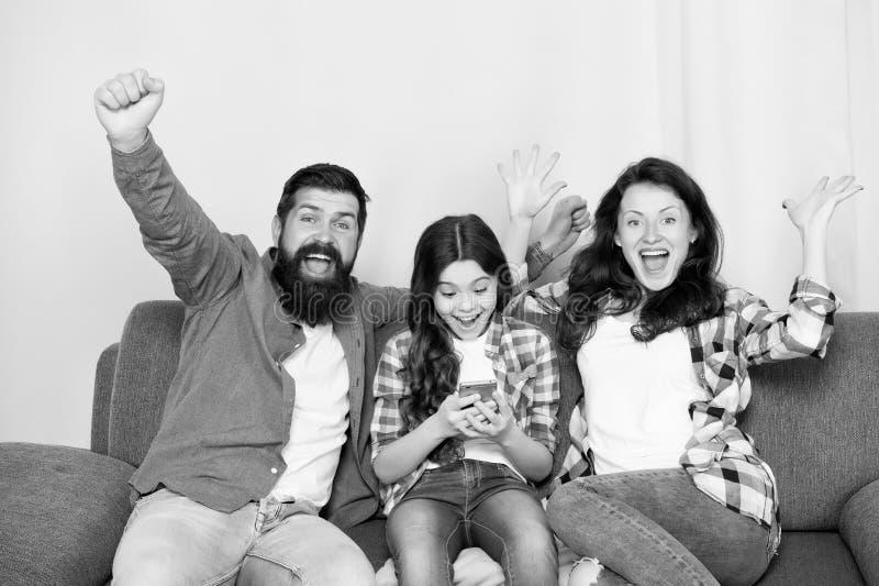 Smartphone del uso de la ni?a del ni?o con los padres Familia amistosa que se divierte junto Pap? de la mam? e hija ocupada que s fotos de archivo