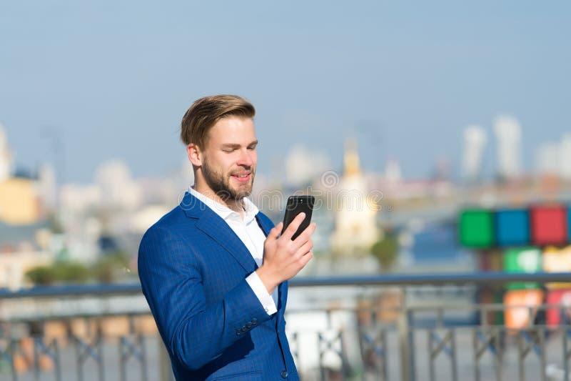 Smartphone del uso del hombre de negocios con sonrisa Hombre feliz con el teléfono móvil en terraza soleada Grandes noticias de n foto de archivo libre de regalías