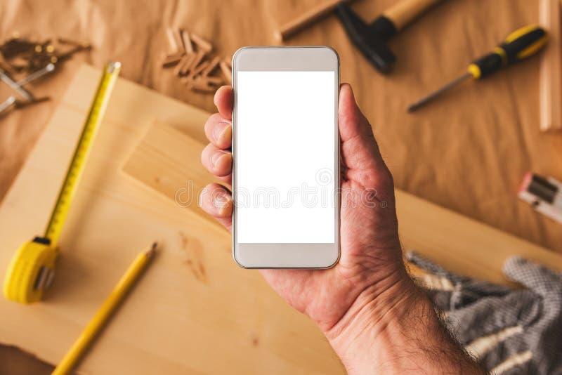 Smartphone della tenuta dell'imprenditore della lavorazione del legno di piccola impresa con derisione sullo schermo immagini stock