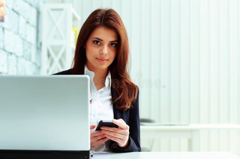 Smartphone della tenuta della donna di affari sul suo posto di lavoro immagine stock