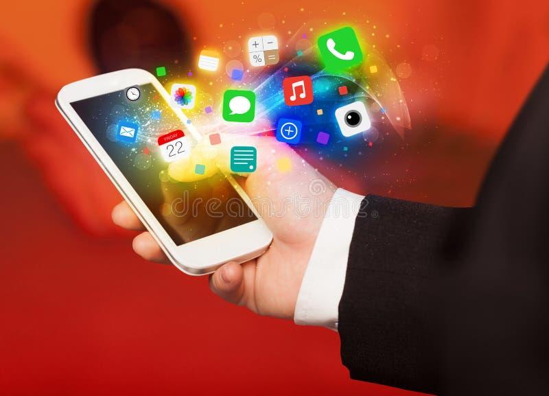 Smartphone della tenuta della mano con le icone variopinte di app fotografia stock libera da diritti