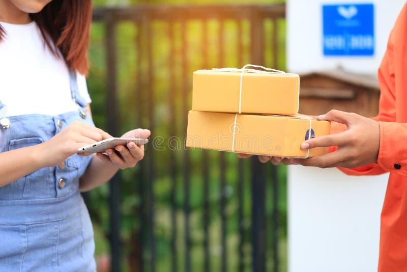 Smartphone della tenuta della mano della giovane donna e ricevuta di firma di deliv fotografie stock libere da diritti