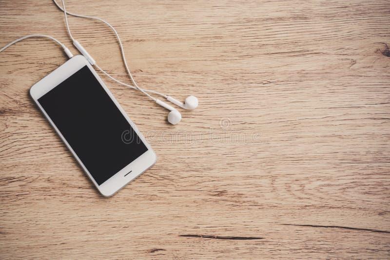 Smartphone dello schermo in bianco con il trasduttore auricolare sulla tavola di legno Vista superiore fotografie stock libere da diritti