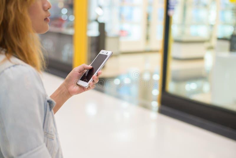 Smartphone di battitura a macchina della tenuta della mano della giovane donna a chiacchierata alla m. di compera fotografie stock