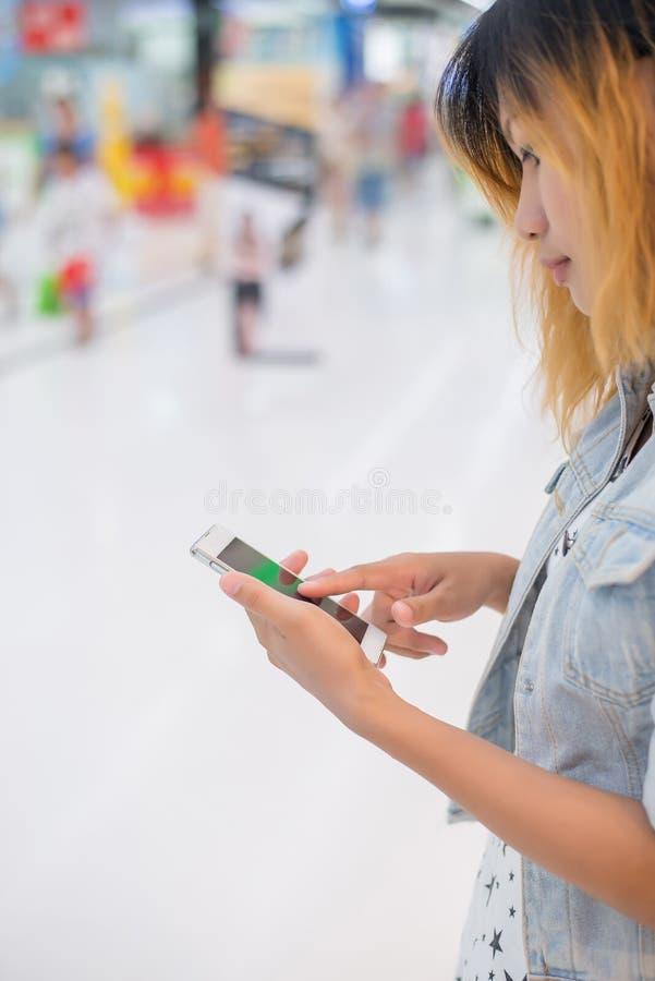 Smartphone di battitura a macchina della tenuta della mano della giovane donna a chiacchierata alla m. di compera fotografia stock libera da diritti