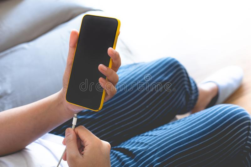 Smartphone di carico della donna Banca di energia Batteria bassa Strumentazione elettronica immagini stock libere da diritti