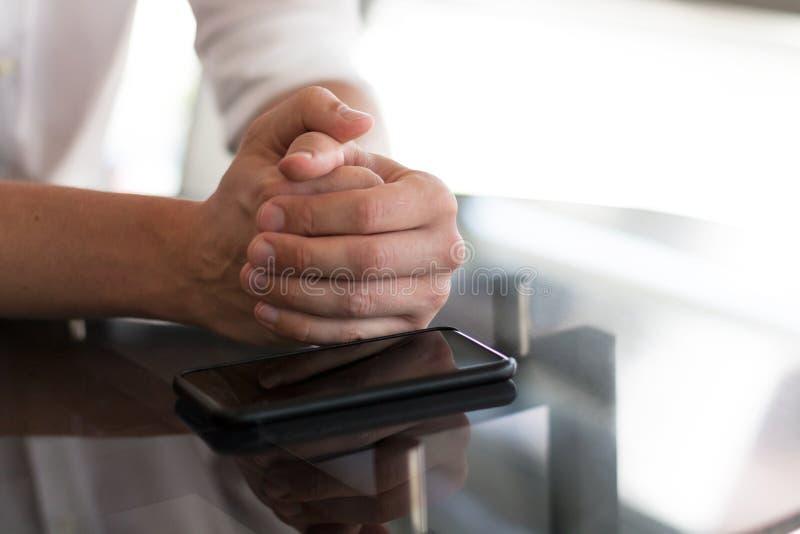 Smartphone di lavoro sui precedenti delle mani del ` s degli uomini immagini stock