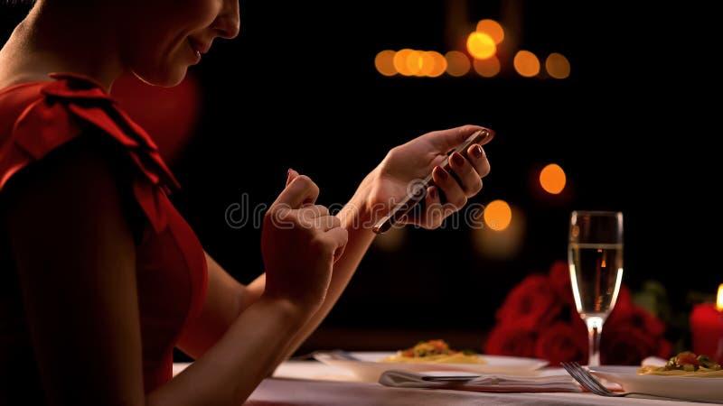 Smartphone di scorrimento della donna elegante in ristorante, uomo aspettante, datante sito Web fotografia stock