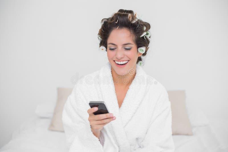 Smartphone di sguardo castana naturale di risata immagine stock