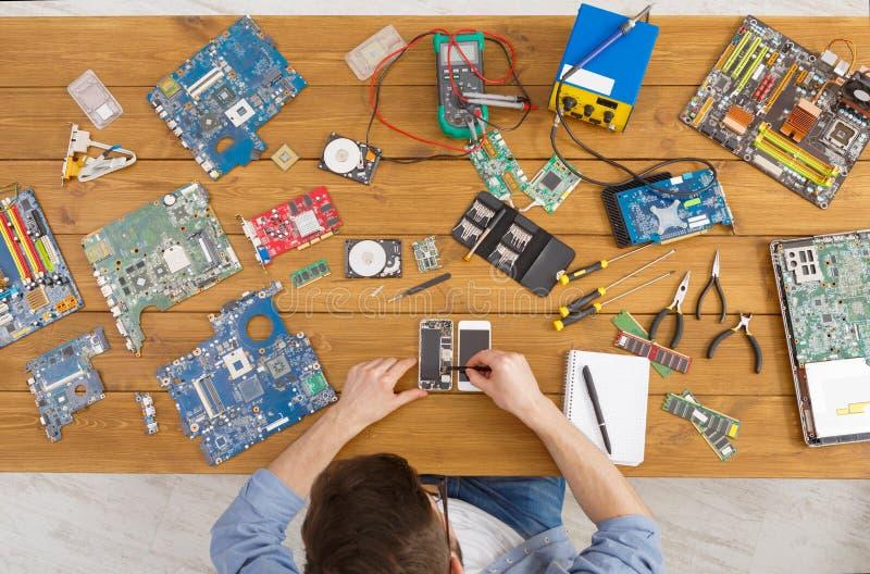 Smartphone di smontaggio dell'uomo nell'officina riparazioni fotografie stock