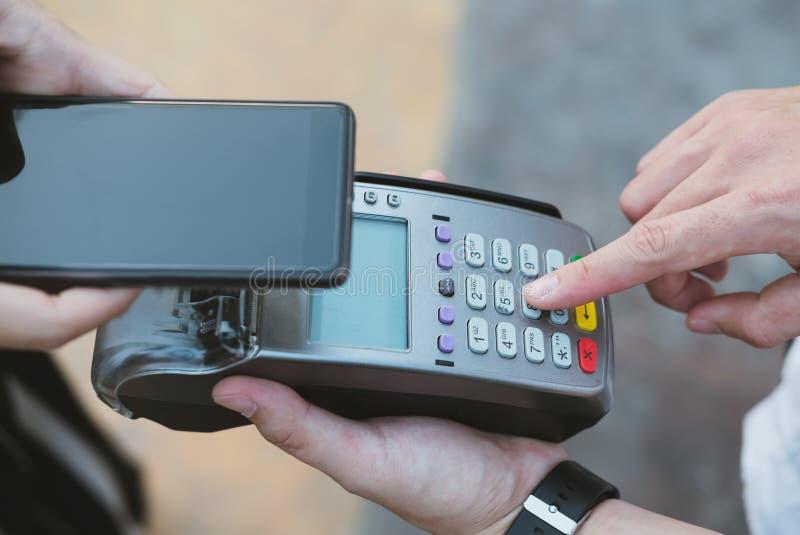 Smartphone di uso della donna per effettuare pagamento mobile con elettronico colto fotografia stock libera da diritti
