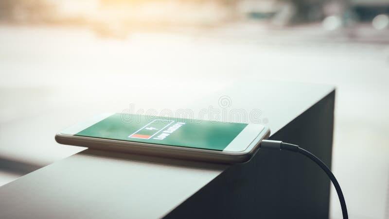 Smartphone die bij bureauruimte laden stock foto