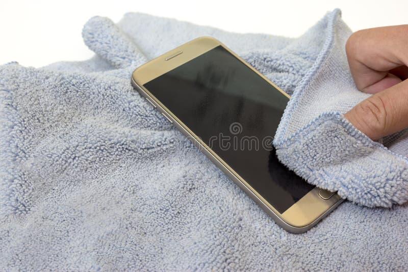 Smartphone die het vuile scherm met blauwe microfiberstof schoonmaken stock foto's