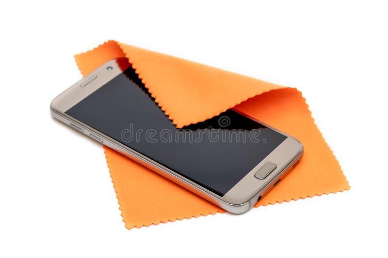 Smartphone die het vuile scherm met oranje die stof schoonmaken, op witte achtergrond wordt geïsoleerd stock fotografie