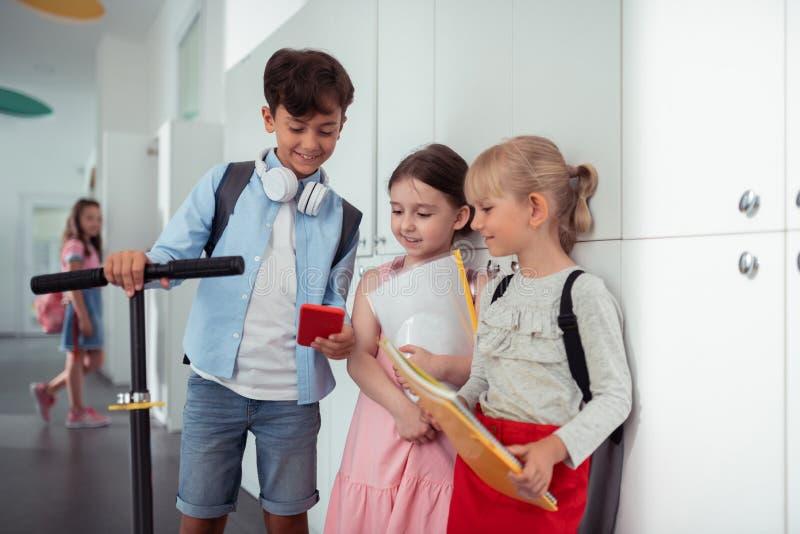 Smartphone die van de jongensholding zijn favoriet spel tonen aan meisjes royalty-vrije stock fotografie
